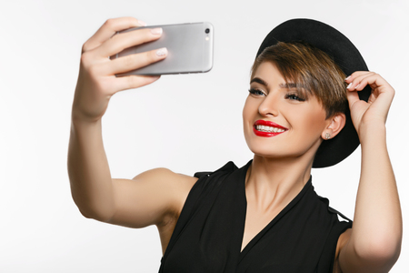 proffessional: A portrait of a very attractive young  lady making  selfie in a photo studio.