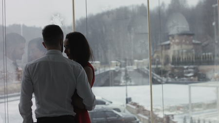 Young couple is standing near the window