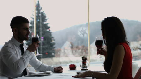 Young happy couple romantic date drink glass of red wine at restaurant, celebrating valentine day Zdjęcie Seryjne