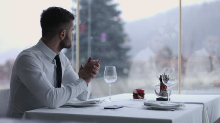 Portrait of a handsome man using smartphone outdoors in restaurant