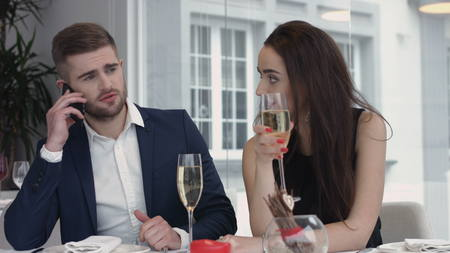 young woman bored to date while  her boyfriend having business cell on mobile phone