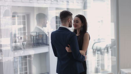 Image of young guy embracing his girlfriend and both looking through window Zdjęcie Seryjne