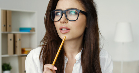 Beautiful young brunette woman in glasses writing with pencil at office during working day
