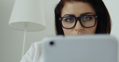 Close up of pretty brunette businesswoman in white shirt and glasses with computer tablet