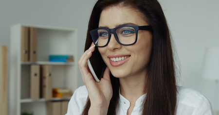Close-up of pretty brunette businesswoman with glasses sitting at desk talking on the phone in office Zdjęcie Seryjne
