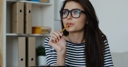 Sexy pretty businesswoman, wearing nerd glasses, holding office notepad and pencil in the mouth