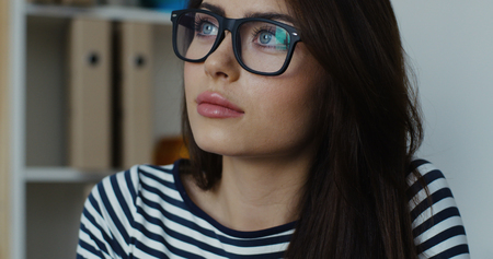 Thoughtful elegant brunette businesswoman, wearing glasses with clipboard in a bright office