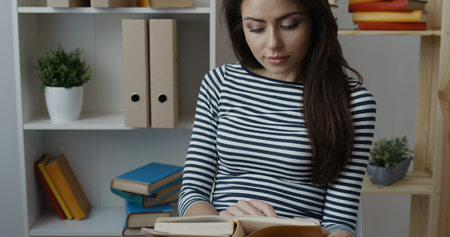 stylish hair: Smiling young brunette woman in striped blouse turning the page of yellow book at office interior