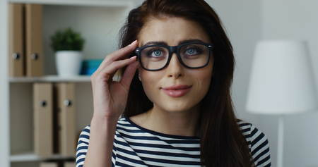 Close-up of sexy brunette smiling businesswoman in striped blouse wearing glasses at office Zdjęcie Seryjne