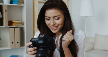 Cute young smiling brunette wearing white shirt sitting holding camera, office interior at background.