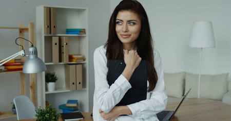 executive apartment: Smiling brunette woman in white shirt standing at office desk with black notepad in hands