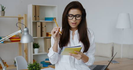 spontaneous expression: Inspired beautiful brunette business woman wearing white shirt and glasses with pencil at lips thinking looking up and writing in notebook at office