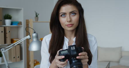 Smiling brunette woman wearing white shirt holding camera and looking at you, office interior at background. Zdjęcie Seryjne