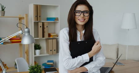Pretty smiling brunette business woman in white shirt wearing glasses holding black notepad in hands