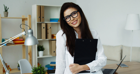 Smiling brunette business woman wearing white shirt and glasses holding black notepad in hands looking at camera, office interior at background. Zdjęcie Seryjne