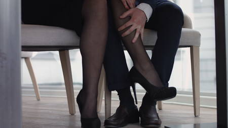 Young couple flirting  with legs at the restaurant under the table