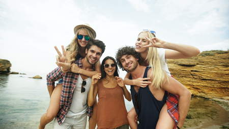 Shot of a group of young friends enjoying a day at the beach