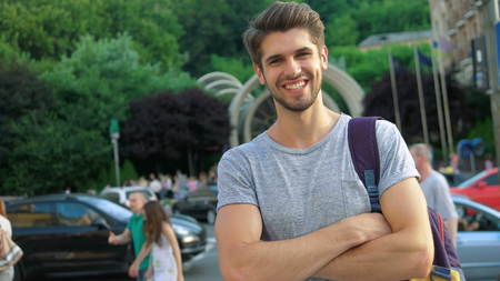 Portrait of a handsome smiling man looking at the camera in city Zdjęcie Seryjne