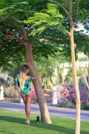 Woman in swimsuit standing near the palm tree. Outdoor summer shooting. Close-up of sensual young girl without makeup in the midst of nature. Summer Vacation Concept.