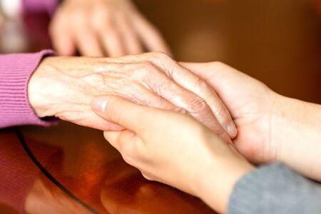 Helping hands. Hands of young adult and senior women. Care and elderly concept.