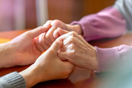 Elderly hands. Helping hands of young adult and senior women. Care and elderly concept. 스톡 콘텐츠