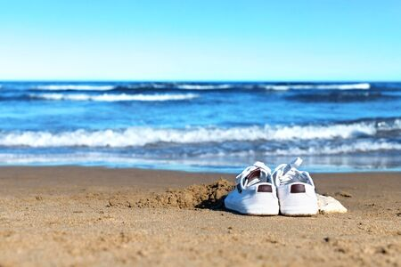 Sneakers on the sand. Alone on the beach. Holiday with coronavirus.