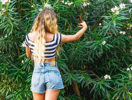 Young beautiful girl with long blond hair taking a selfie on smartphone in park. Back view.
