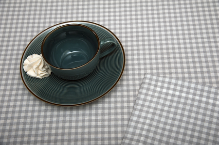 Ceramic cup and a saucer with a meringue on a table covered with a linen tablecloth Stock Photo
