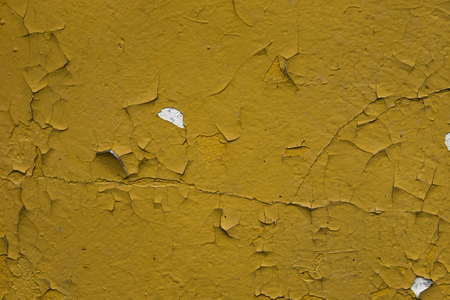 Texture background of bright yellow peeling paint