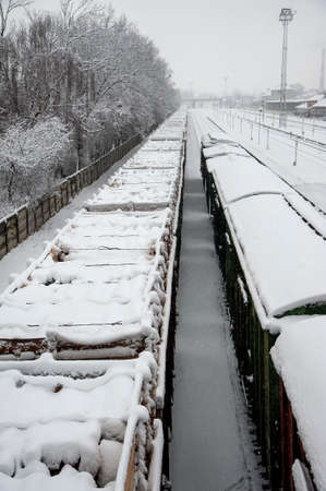 Freight railway wagons are covered by a thick snow layer on the railway tracks. Stockfoto