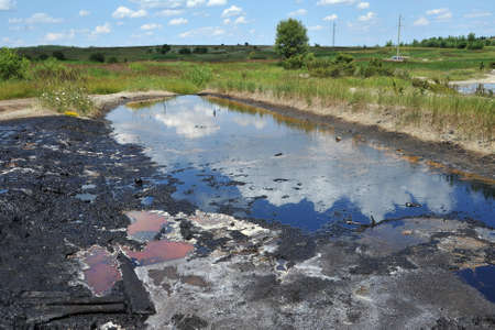 Industrial oil pollution on the surface of the soil near the old oil wells is an environmental catastrophe.