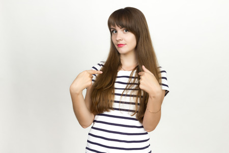 disbelief: Portrait of a pretty woman shows a finger on the are you talking to me?  over gray background Stock Photo