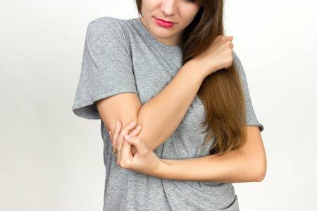 肘の痛み。美しい女性は、彼女の肘を保持しています。痛みの概念クローズ アップ黒と白と赤のアクセント