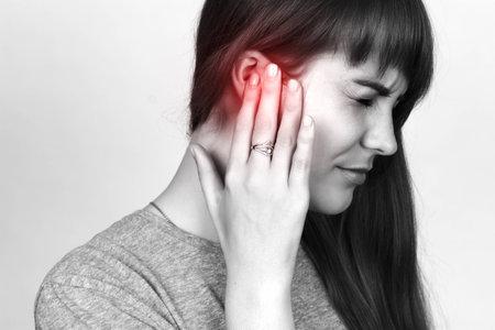 젊은 여자는 아픈 귀가있다. 회색 배경 위에 근접 촬영에서 고통을 소녀. 검은 색과 흰색의 빨간 액센트 스톡 콘텐츠