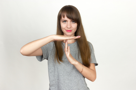 Portrait of a pretty woman standing with hands crossed and showing stop gesture  over gray background Stock Photo