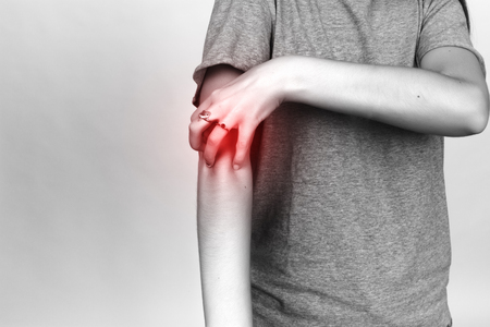 malaria: Girl in grey shirt scratching her arm. Scabies. Scratch the hand  over gray background. Black and white with red accent