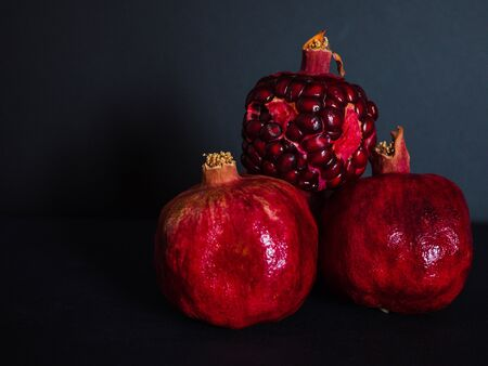 red pomegranate whole and cut on a dark black background