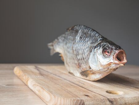 Dried smoked fish smelt, on a wooden board. Stock Photo