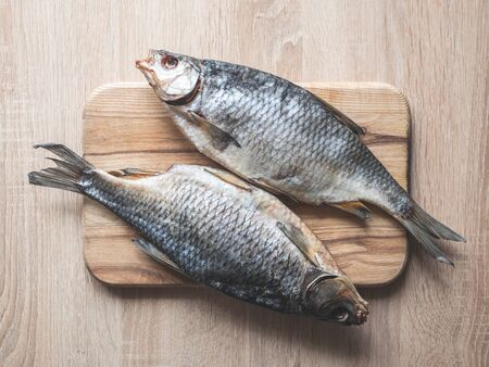 Dried smoked fish smelt, on a wooden board.