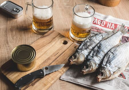 Light beer and smoked dry fish on the table.