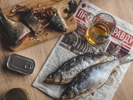 Light beer and smoked fish on the table.