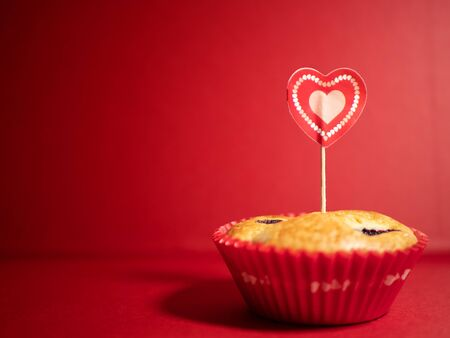 Muffins with blueberries and raspberries. Cupcakes with Valentine's Day decor. Flat lay. Banner.