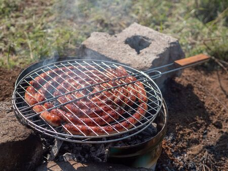 Bavarian sausages grilling on barbecue grill. BBQ outside.