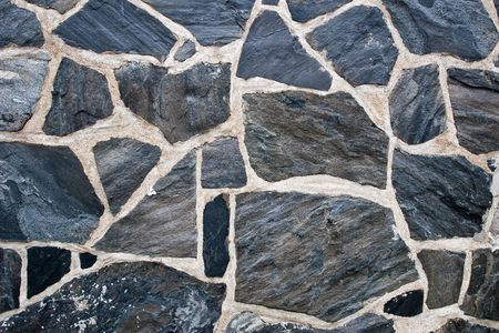 Stone wall fixed with cement with cracks photo