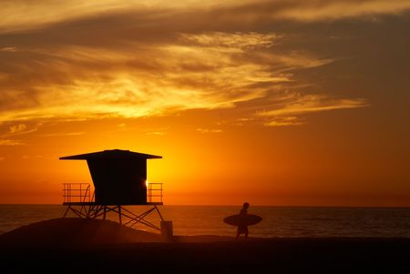 Lifeguard tower with setting sun on the horizon and the silhouette of the surfer. photo