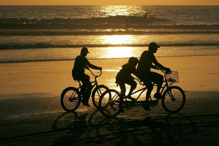 Family riding bikes along the beach at sunset. photo