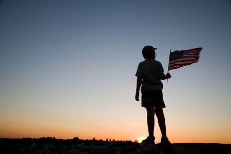 banderas americanas: Joven muchacho la celebraci�n de una bandera americana en la puesta de sol. Foto de archivo