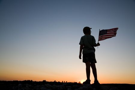 salut: Young boy holding an American flag at sunset.