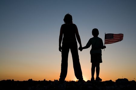 Mother holding her son with an American flag at sunset.