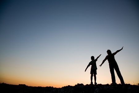 母と息子の日没で飛行するふりをしています。